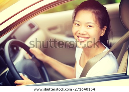 young asian woman driver driving a car - stock photo