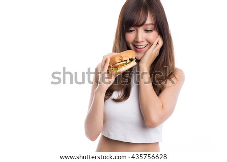 Young asian woman eating burger on white background, unhealthy eating and diet concepts. - stock photo