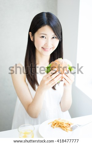 Young Asian woman eating hamburger