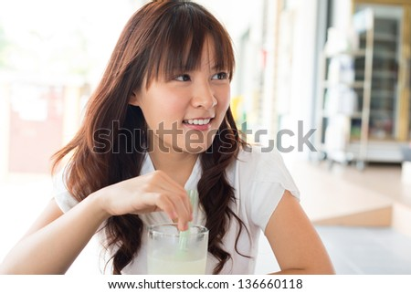 Young Asian woman enjoying drinks with friend at cafe. - stock photo