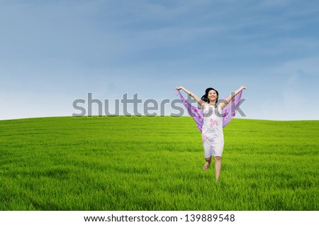 Young asian woman enjoying freedom by sarong on the meadow