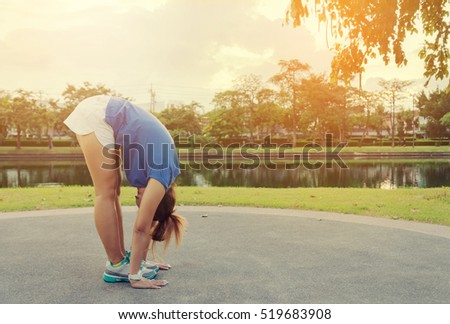 Young Asian Woman Exercise Hand Touching Her Foot in Outdoor Public Park Background - Lifestyle Sport Concept