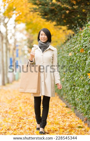 Young Asian woman having shopping bags in Autumn city. - stock photo
