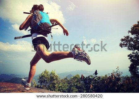 young asian woman hiker running on mountain peak cliff - stock photo