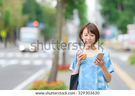 Young Asian woman holding a coffee cup and a smart phone. - stock photo