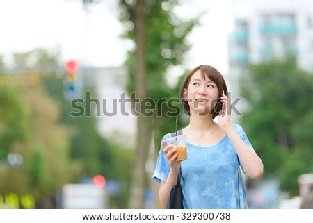 Young Asian woman holding a coffee cup and talking with smart phone. - stock photo