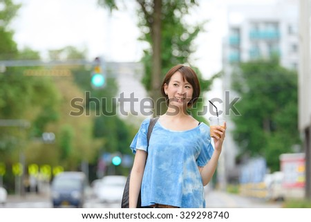 Young Asian woman holding a coffee cup and walking on a street. - stock photo