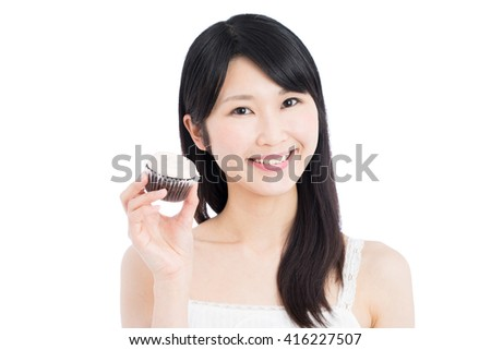 Young Asian woman holding a cupcake isolated on white background