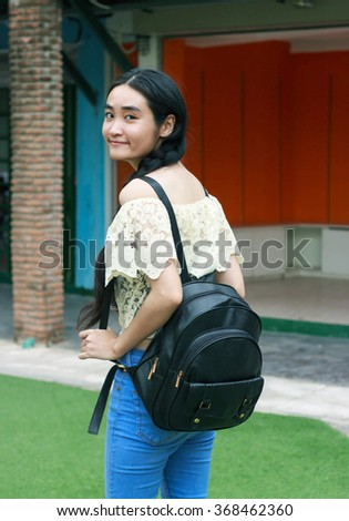 Young Asian woman holding bag while walking. - stock photo
