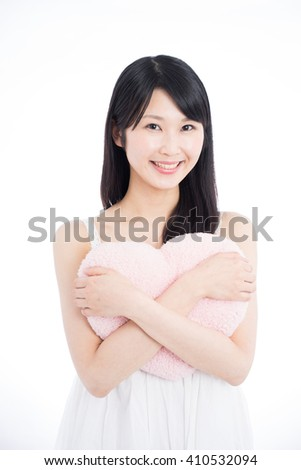 Young Asian woman holding pink heart, isolated on white background