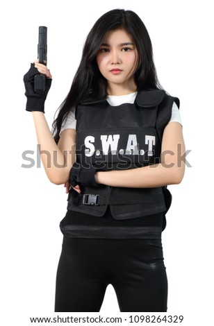 young asian woman in black clothes and bulletproof vest holding gun