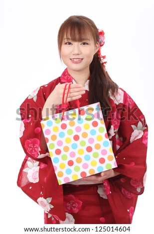 Young asian woman in clothes of kimono with shopping bag - stock photo
