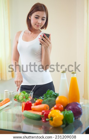 Young asian woman In Kitchen Following Recipe On Mobile phone - stock photo