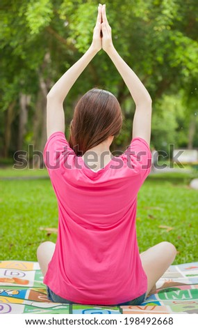 Young asian woman in pink sitting on grass and practicing yoga - stock photo