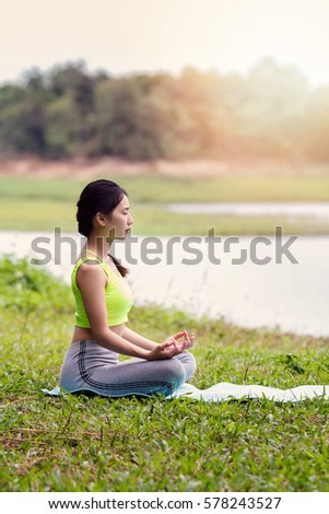 Young asian woman in sportswear meditating on yoga mat