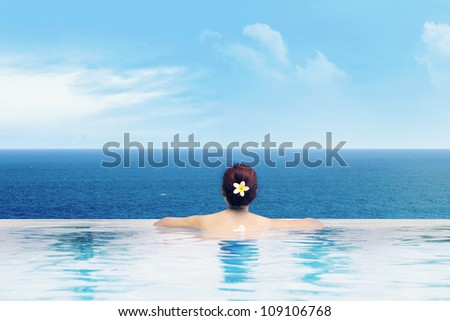 Young asian woman in the infinity pool enjoying the ocean view