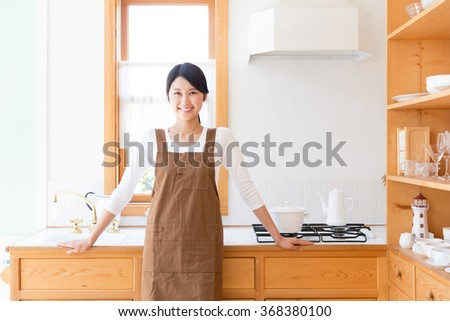 young asian woman in the kitchen - stock photo
