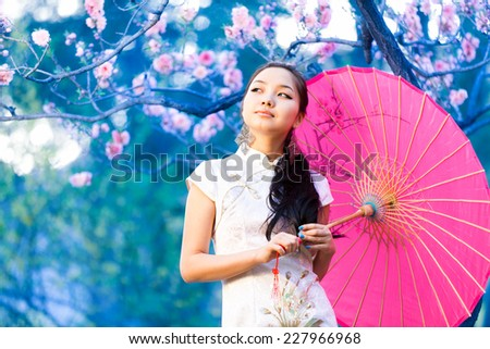 Young asian woman in the rays of the spring sun. - stock photo
