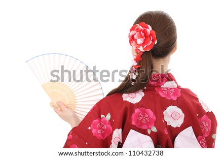 Young asian woman in traditional clothes of kimono holding paper fan - stock photo
