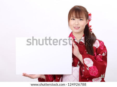 Young asian woman in traditional clothes of kimono holding white board - stock photo