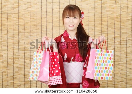 Young asian woman in traditional clothes of kimono with shopping bag - stock photo