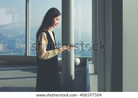 Young Asian woman is reading text message in network via smart phone,while is standing in modern interior with cityscape New York view.Female office worker of successful company is using mobile device