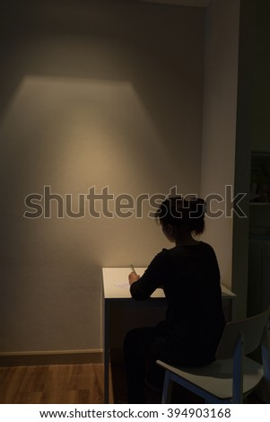 Young Asian woman is suffering alone from a severe depression- long exposure technique - stock photo