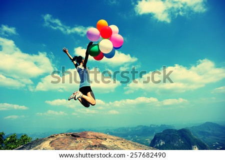 young asian woman jumping on mountain peak rock with colored balloons  - stock photo