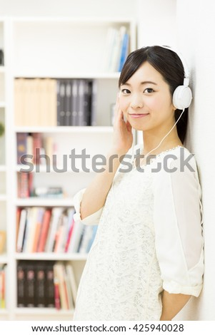 young asian woman listening music in the room