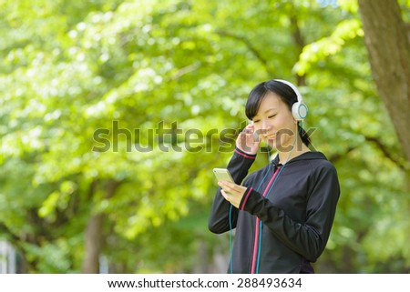 Young Asian woman listening to music with smart phone during exercise. - stock photo