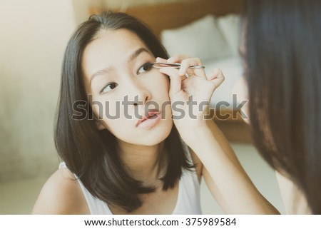 Young asian woman make up yourself looking mirror - vintage soft effect and light filter processing - stock photo