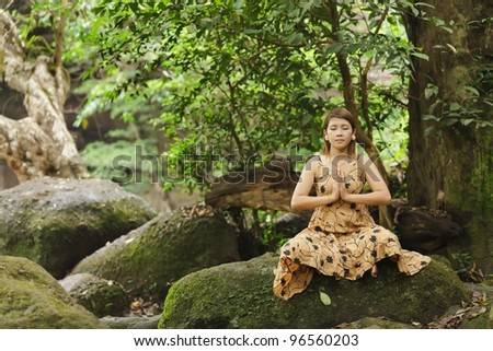 young asian woman meditating in wild forest, thailand