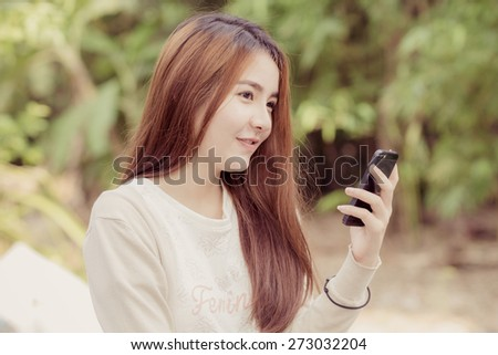 Young asian woman playing smartphone at outdoor - stock photo