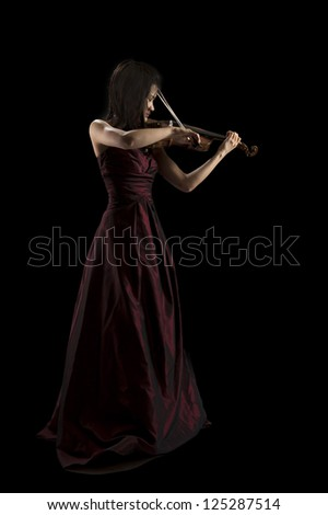 young asian woman playing the violin on black background - stock photo