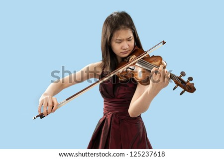 young asian woman playing the violin on blue background - stock photo