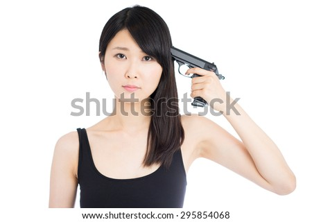 young Asian woman pointing a gun on herself - stock photo