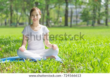 Young  Asian woman practicing yoga  at the Green park ,  Healthy lifestyle Concept.