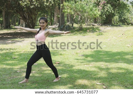 Young asian woman practicing yoga outdoors in morning park. Concept of healthy lifestyle and relaxation