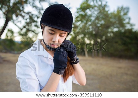 Young asian woman prepare for a horse riding