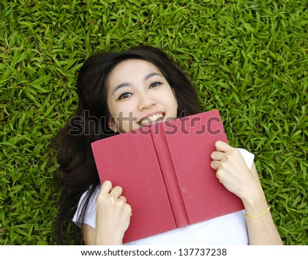 young asian woman reading book in the park - stock photo