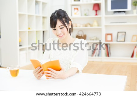 young asian woman reading book in the room