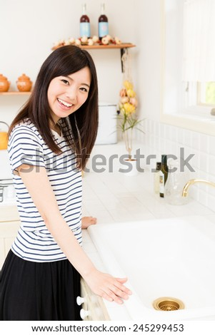 young asian woman relaxing front of house