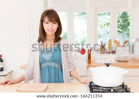 young asian woman relaxing in the kitchen room
