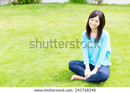 young asian woman relaxing in the lawn - stock photo