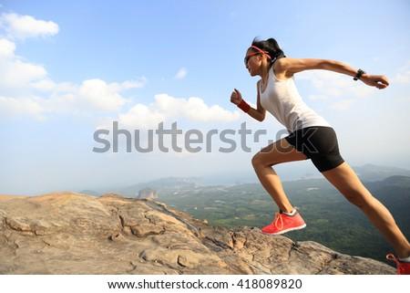 young asian woman runner running on mountain peak - stock photo