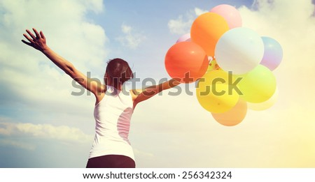 young asian woman  running  with colored balloons  - stock photo