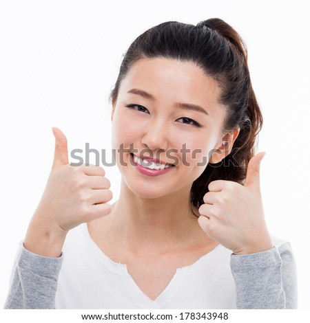 Young Asian woman showing thumb close up shot isolated on white background. - stock photo
