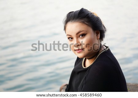 young asian woman sitting by the water. with copy space. - stock photo