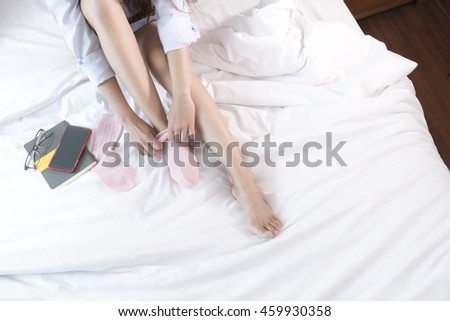 Young Asian woman sitting on a bed wearing socks. Top view. cool tone, low contrast.