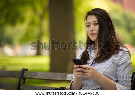 Young Asian woman sitting park bench texting cell phone